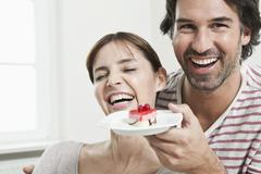 Germany, Berlin, Man surprising woman with serving cake - stock photo