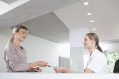 Stock Photo of Germany, Patient giving insurance card to receptionist in dental office