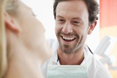 Germany, Dentist and patient in clinic, smiling - stock photo