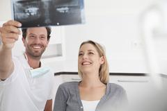 Germany, Dentist and patient viewing x ray - stock photo
