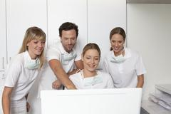 Germany, Dentist and assistance looking at screen Stock Photos