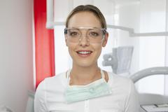 Germany, Dentist with safety glasses in dental office - stock photo
