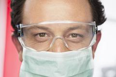 Germany, Dentist with safety glasses and surgical mask in dental office - stock photo