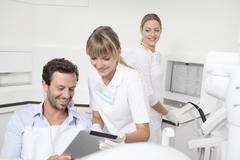 Germany, Dentist showing clipboard to patient Stock Photos