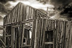 Spooky cabin sepia toned with dramatic sky in background Stock Photos