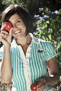Stock Photo of Austria, Salzburg, Flachau, Woman holding tomatoes in front of her eyes, smiling