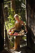 Austria, Salzburg, Flachau, Young woman holding fruit in tray, smiling, portrait - stock photo