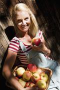 Austria, Salzburg, Flachau, Young woman holding apples, smiling, portrait Stock Photos
