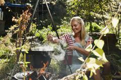 Itävalta, Salzburgin alue, Flachau, Nuori nainen ruoanlaitto takka, hymyilee Kuvituskuvat