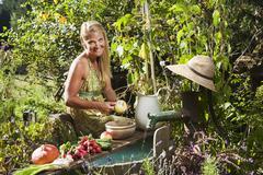 Austria, Salzburg, Flachau, Young woman cutting fruits, smiling, portrait - stock photo