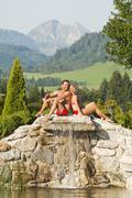 Austria, Salzburg County, Couple sitting on stonewall at hotel garden Stock Photos