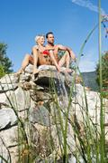 Stock Photo of Austria, Salzburg County, Couple sitting on stonewall at hotel garden