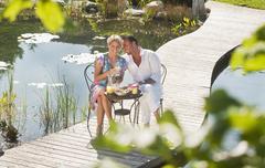 Stock Photo of Austria, Salzburg County, Couple having breakfast on bridge over pond
