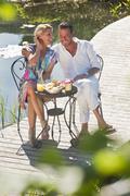 Austria, Salzburg County, Couple having breakfast on bridge over pond - stock photo