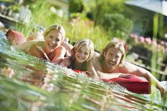 Family on airbed in natural pool - stock photo