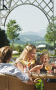 Family eating icecream in hotel garden - stock photo