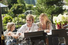 Perhe istuu terassilla hotellin puutarhassa Kuvituskuvat