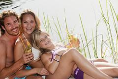 Family sitting near pool in hotel garden - stock photo