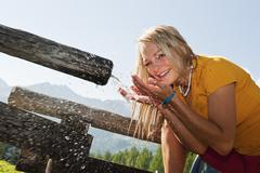 Austria, Salzburg County, Young woman drinking water from water trough, portrait - stock photo