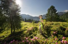 Austria, Salzburg County, Young woman standing in alpine meadow and watching Stock Photos