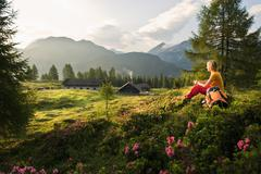 Austria, Salzburg County, Young woman sitting in alpine meadow and watching - stock photo