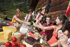 Austria, Salzburg County, Men and women sitting at alpine hut, listening to - stock photo