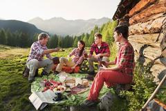 Austria, Salzburg County, Men and women having picnic near alpine hut at sunset Stock Photos