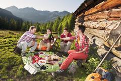 Austria, Salzburg, Men and women having picnic near alpine hut at sunset Stock Photos
