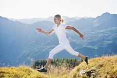 Austria, Salzburg County, Young woman running and jumping in alpine meadow Stock Photos