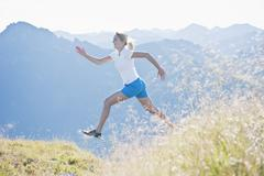 Austria, Salzburg County, Young woman running and jumping in alpine meadow - stock photo
