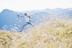 Austria, Salzburg County, Young woman with nordic walking pole and jumping in Stock Photos