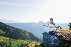 Austria, Salzburg County, Young woman sitting on rock and doing meditation Stock Photos