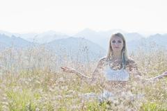 Austria, Salzburg County, Young woman sitting in alpine meadow and doing Stock Photos