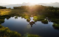 Stock Photo of Austria, Salzburg County, Young woman sitting near mountain lake and doing