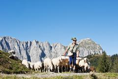 Stock Photo of Austria, Salzburg County, Shepherd herding sheep on mountain