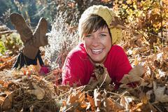 Austria, Salzburg County, Young woman lying on autumn leaves, smiling, portrait Stock Photos