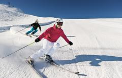 Austria, Salzburg, Young couple skiing on mountain - stock photo