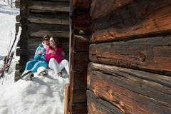 Austria, Salzburg, Young couple sitting in front of alpine hut - stock photo