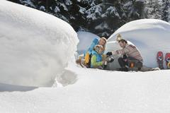 Austria, Salzburg County, Family sitting near igloo Stock Photos