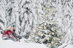 Austria, Salzburg County, Boy and girl watching christmas tree in snow - stock photo