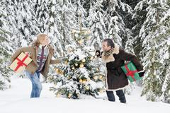 Austria, Salzburg County, Couple holding christmas gift in snow, smiling - stock photo