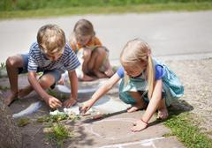Germany, Bavaria, Group of children drawing on walkway with chalk - stock photo