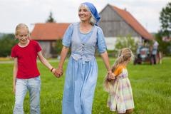 Germany, Bavaria, Grandmother with children walking in front of farmhouse Stock Photos