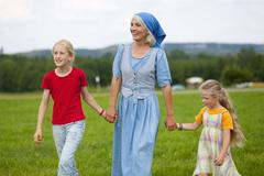Germany, Bavaria, Grandmother with children walking through meadow Stock Photos