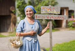 Germany, Bavaria, Mature woman standing next to sign board Stock Photos