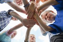 Germany, Bavaria, Group of children putting hands together - stock photo
