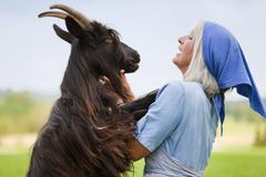 Germany, Bavaria, Mature woman with goat on farm Stock Photos