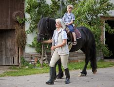 Germany, Bavaria, Mature woman leading boy on horse - stock photo