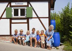 Germany, Bavaria, Woman sitting with group of children in front of small house Stock Photos