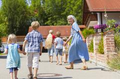 Germany, Bavaria, Mature woman with children dancing on street - stock photo